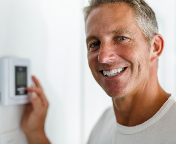 Smiling man in white t-shirt, standing in front of thermostat