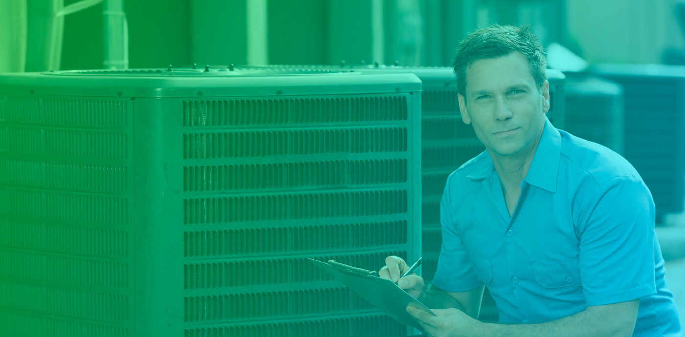 Smiling man kneeling beside air conditioning unit holding a clipboard and pen